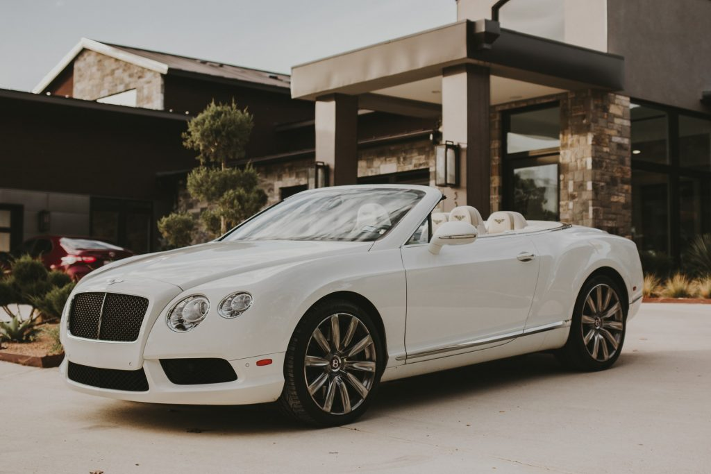 A pristine-looking white Bentley convertible outside of a modern mansion
